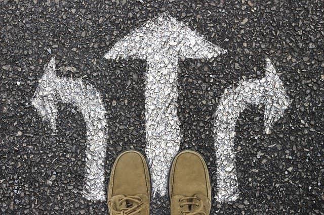 Imagem de pessoa parada em frente a setas indicando direções opostas