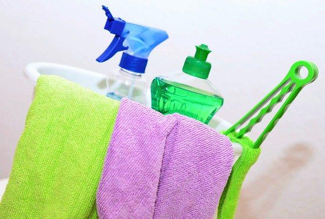 Imagem de balde, com panos, escova e produtos de limpeza.